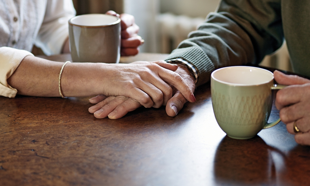 Two people holding hands and holding tea