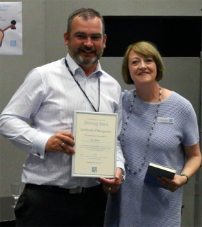 Alan Campbell receiving his graduation certificate from Catherine Muirden