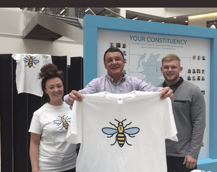 Gina Jacobs and Council President Nick Crofts, selling Manchester Bee t-shirts, raised over £2,180