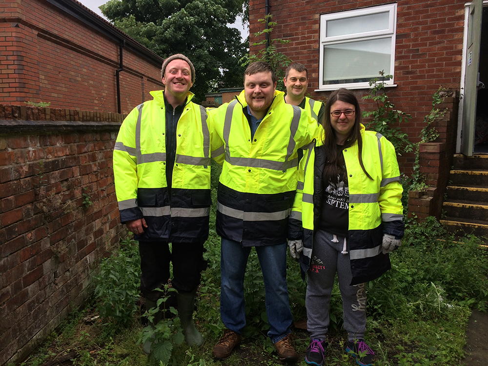 Colleagues from Marple Co-op helping to clear an overgrown garden for Marple Senior Citizens' Association