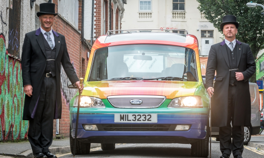 Two Funeralcare colleagues flank a rainbow hearse used for Brighton Pride