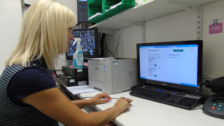 Sarah Kavanagh store manager typing on her computer