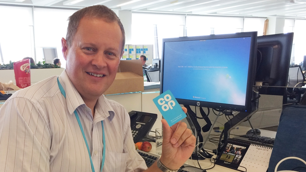 Kevin Ferneyhough holding up a colleague membership card at his desk
